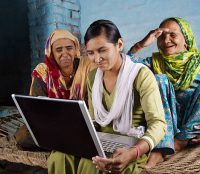 Village Women Working on Laptop with her Younger Daughter and Sitting on Charpai. The Shot is Taken using Studio Lights
